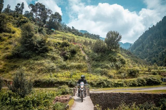 Royal Enfield Unroad Himachal - A Himalayan rider crosses a bridge heading towards a forest trail