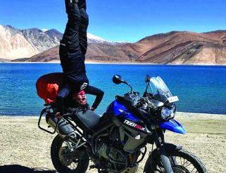 Sangeetha Jairam yoga headstand on a BMW GS